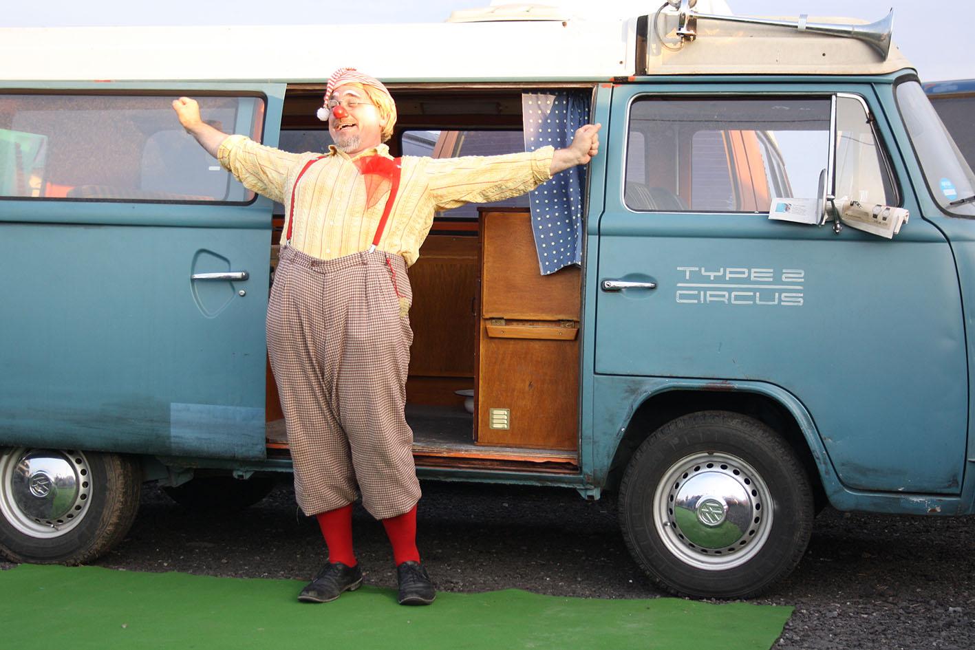 Clown Tomtom steht glücklich vor seinem VW Bus